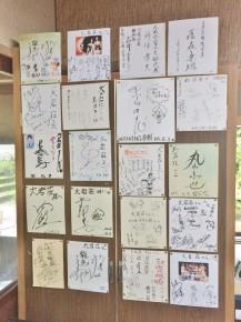 壁に飾られた大勢の有名人のサイン