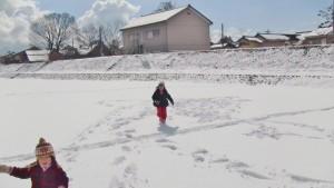 河川敷で雪遊びをする子ども達
